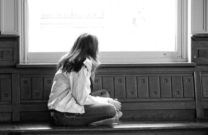 窓の外を見つめるアジア人女性