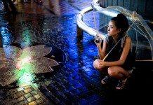 夏の雨、夜、傘をさした女性