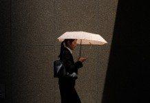 傘をしてスマホを見ながら歩く女子就活生