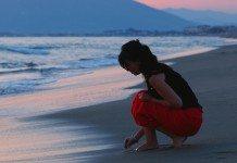 砂浜でしゃがむ女性