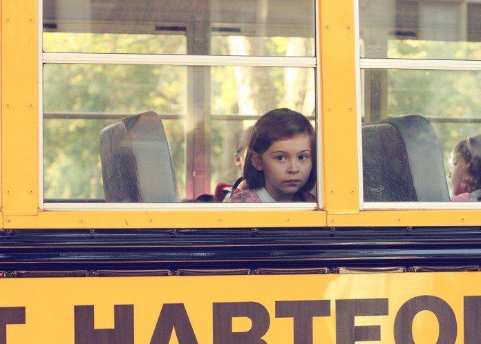 スクールバスから外を見つめる女の子